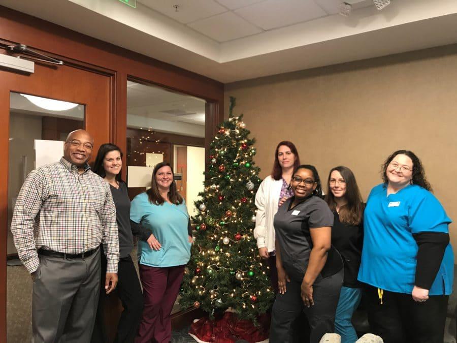 Cary Ortho employees gathered around a Christmas tree